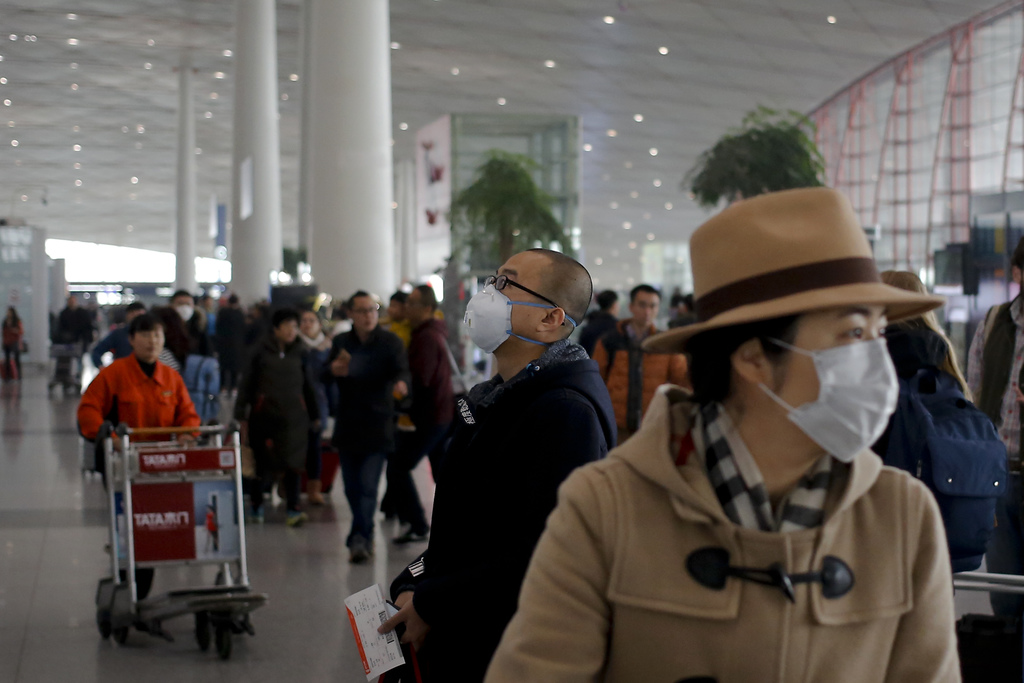 A man wearing a mask for protection against air pollution looks at a flight information board at the Beijing Capital International Airp...