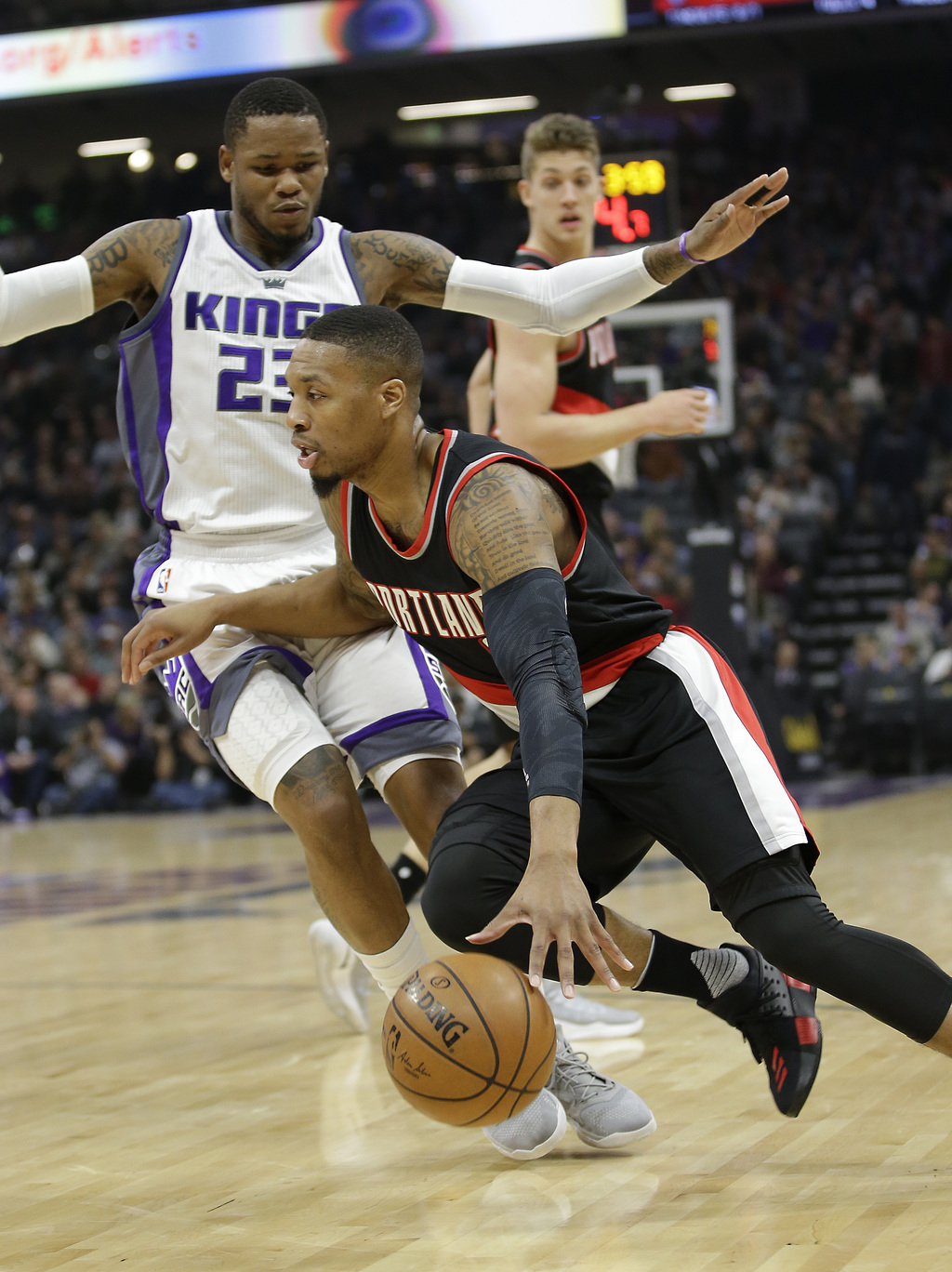Portland Trail Blazers guard Damian Lillard, right, drives against Sacramento Kings guard Ben McLemore during the first quarter of an N...