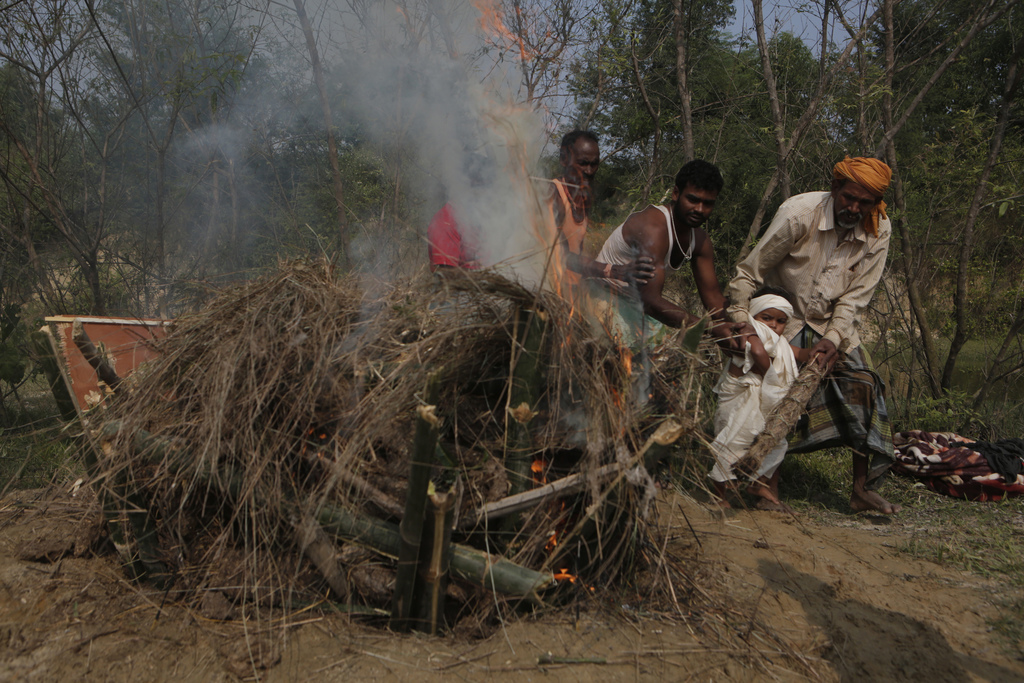 In this Wednesday, Nov. 23, 2016 photo, a priest helps Shivendra Kumar Mandal, 3, nicknamed Siban, perform cremation rituals before lig...