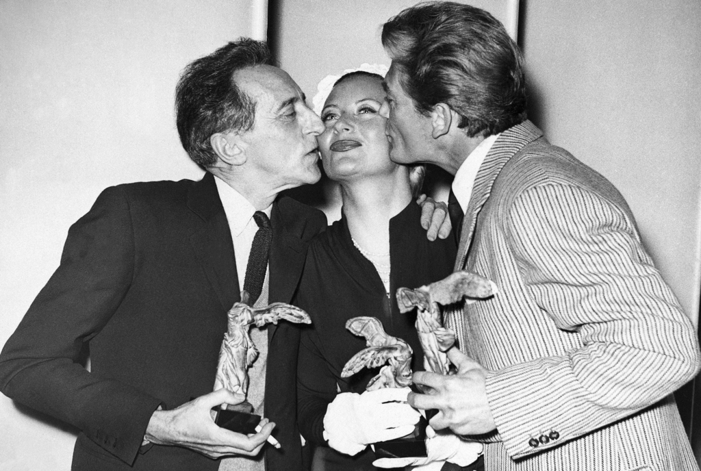 FILE - In this April 8, 1951 file photo, Jean Cocteau, left, and Jean Marais kiss Michele Morgan whilst holding their awards at Cannes ...