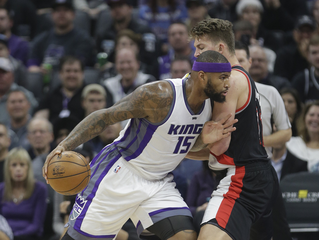 Sacramento Kings forward DeMarcus Cousins, left, goes to the basket against Portland Trail Blazers' Meyers Leonard during the first qua...