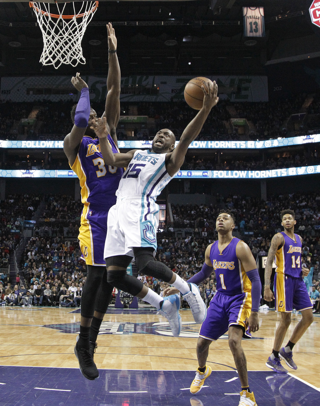 Charlotte Hornets' Kemba Walker (15) drives against Los Angeles Lakers' Julius Randle (30) during the second half of an NBA basketball ...