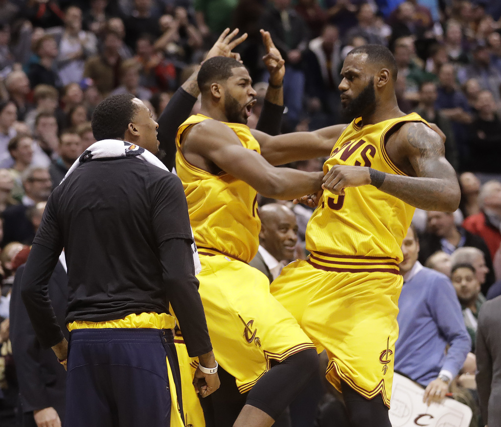 Cleveland Cavaliers' LeBron James is congratulated by teammate Tristan Thompson after making a three-point basket during overtimeof an ...