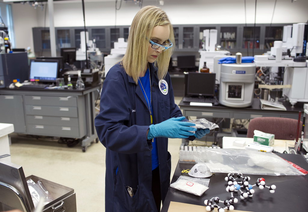 In this Aug. 9, 2016, photo, forensic chemist Emily Dye handles evidence, seized in drug raids, which contains fentanyl analogs at the ...