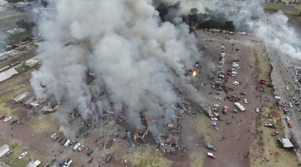 This image made from video provided by APTN, shows a view from a drone of smoke billowing from the San Pablito Market, where an explosi...