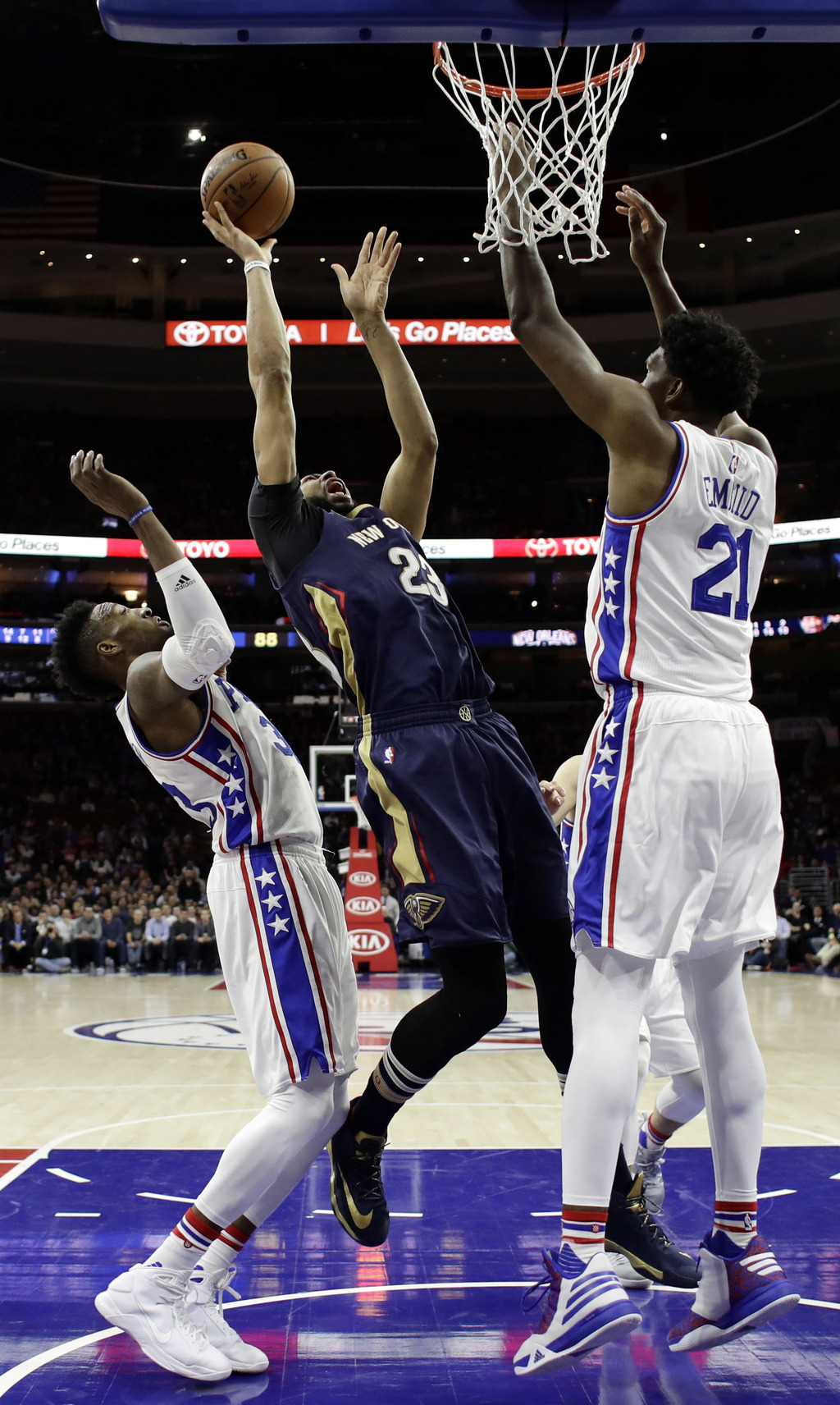 New Orleans Pelicans' Anthony Davis, center, goes up for a shot between Philadelphia 76ers' Robert Covington, left, and Joel Embiid dur...