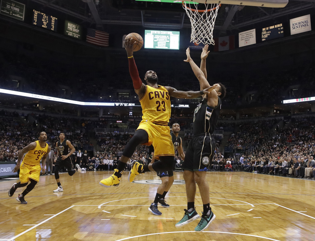 Cleveland Cavaliers' LeBron James shoots over Milwaukee Bucks' Malcolm Brogdon during the first half of an NBA basketball game Tuesday,...