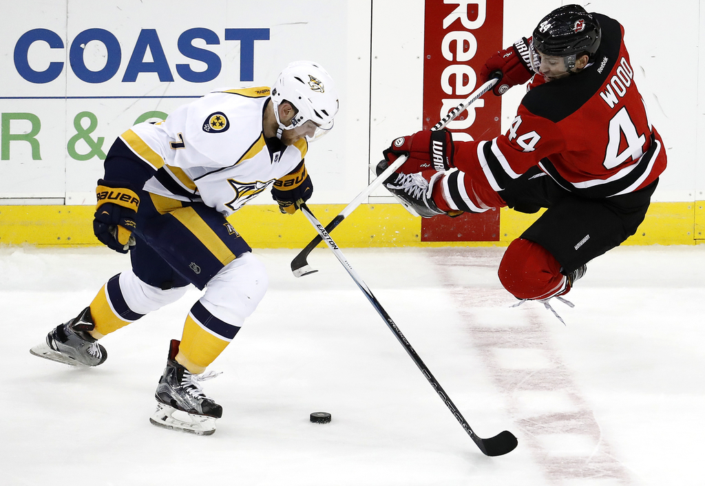 New Jersey Devils left wing Miles Wood, right, goes flying while competing for the puck with Nashville Predators defenseman Yannick Web...
