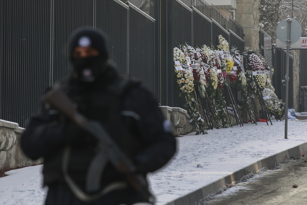 Wreaths are left on the the road leading to the Russian embassy in Ankara, Turkey, Wednesday, Dec, 21, 2016, as a Turkish police office...