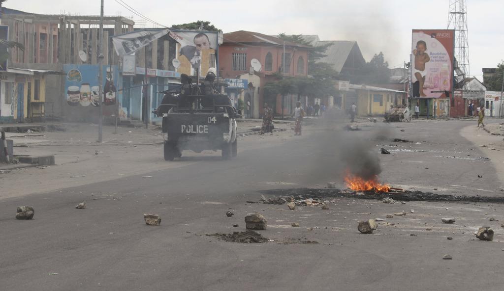 Policemen drive past burning debris during protests in Kinshasa, Democratic Republic of Congo, Tuesday, Dec. 20, 2016. Human Rights Wat...