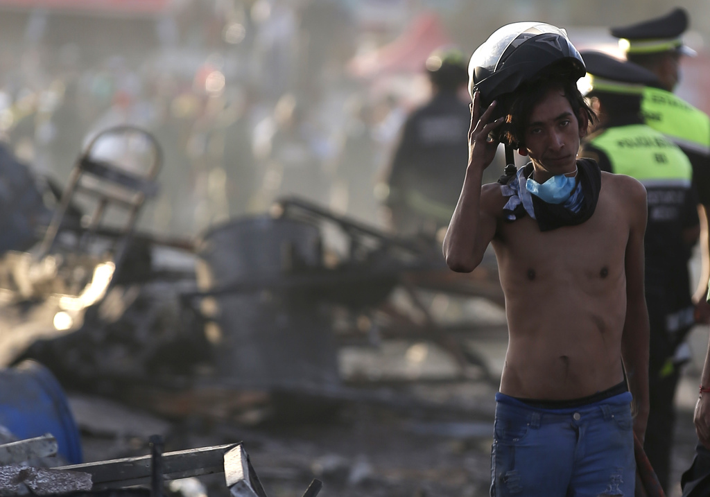 A boy takes his helmet off as he pauses while working at the scorched ground of the open-air San Pablito fireworks market, in Tultepec,...