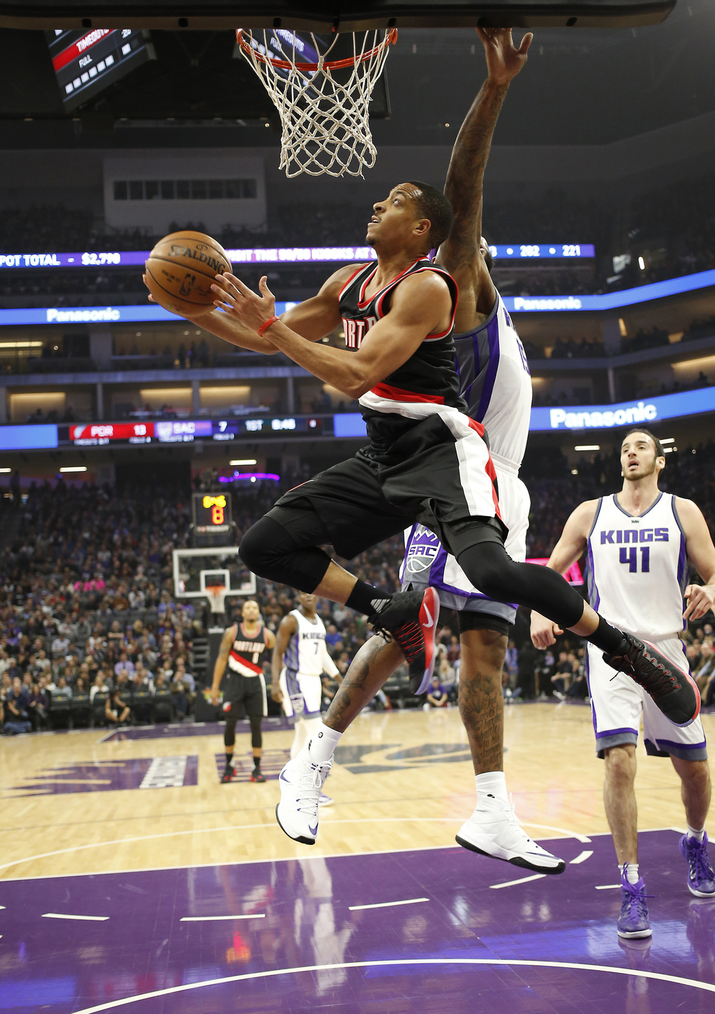 Portland Trail Blazers guard C.J. McCollum, left, drives to the basket past Sacramento Kings forward DeMarcus Cousins, second rom right...