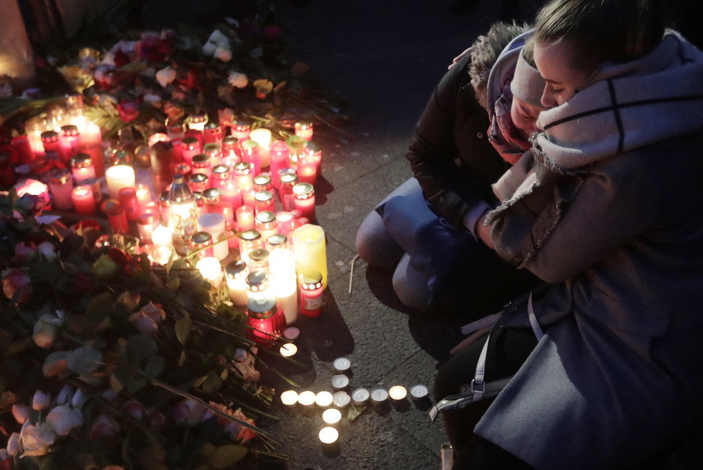 Two women mourn beside candles in Berlin, Germany, Tuesday, Dec. 20, 2016, the day after a truck ran into a crowded Christmas market ne...