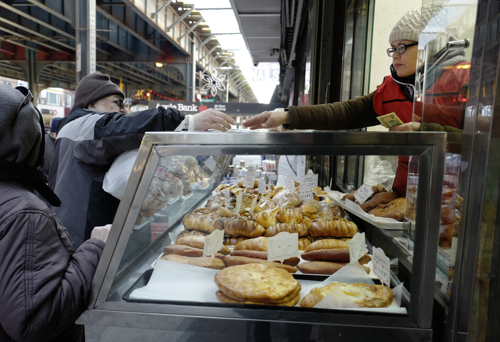 In this Dec. 16, 2016 photo, a clerk leans through a bakery window to make change for a customer in the Brooklyn borough of New York. D...