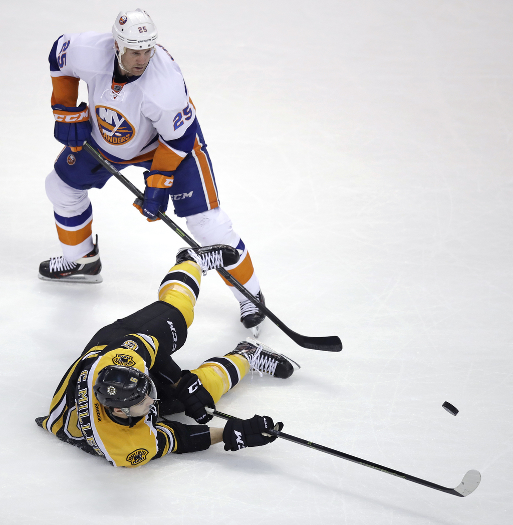 Boston Bruins defenseman Colin Miller, bottom, tries to control the puck against New York Islanders left wing Jason Chimera (25) during...