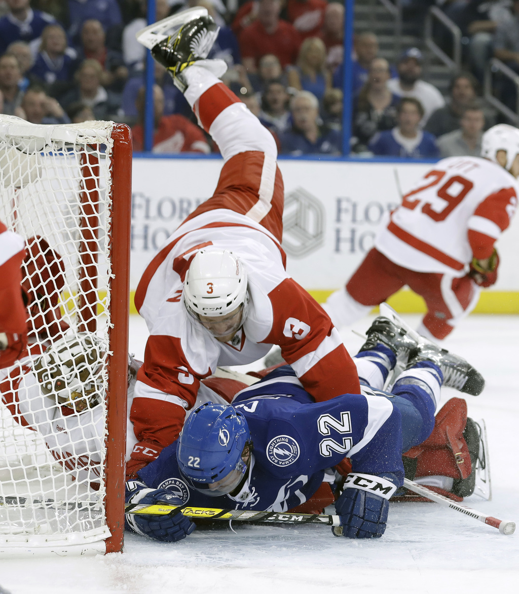 Detroit Red Wings defenseman Nick Jensen (3) knocks down Tampa Bay Lightning right wing Erik Condra (22) on top of Red Wings goaltender...