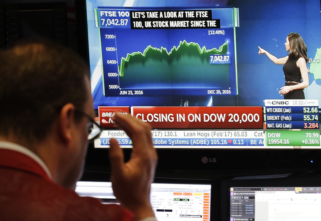 A stock trader follows stock information on electronic screens at the New York Stock Exchange, Tuesday, Dec. 20, 2016, in New York. Gai...