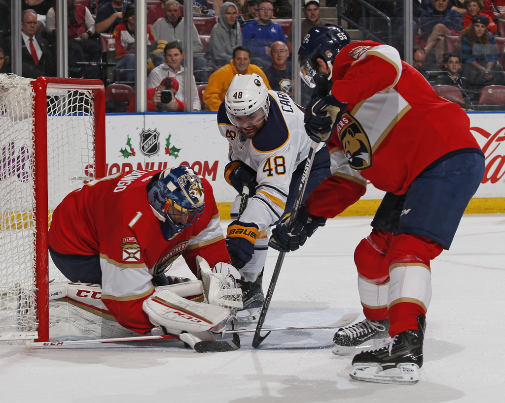 Florida Panthers defenseman Jason Demers (55) helps defend the net as Florida Panthers goaltender Roberto Luongo (1) stops a shot by Bu...