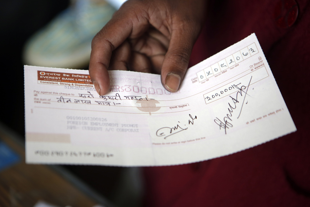 In this Tuesday, Dec 20, 2016 photo, Saro Kumari Mandal, 26, holds a cheque received as compensation from the Foreign Employment Promot...