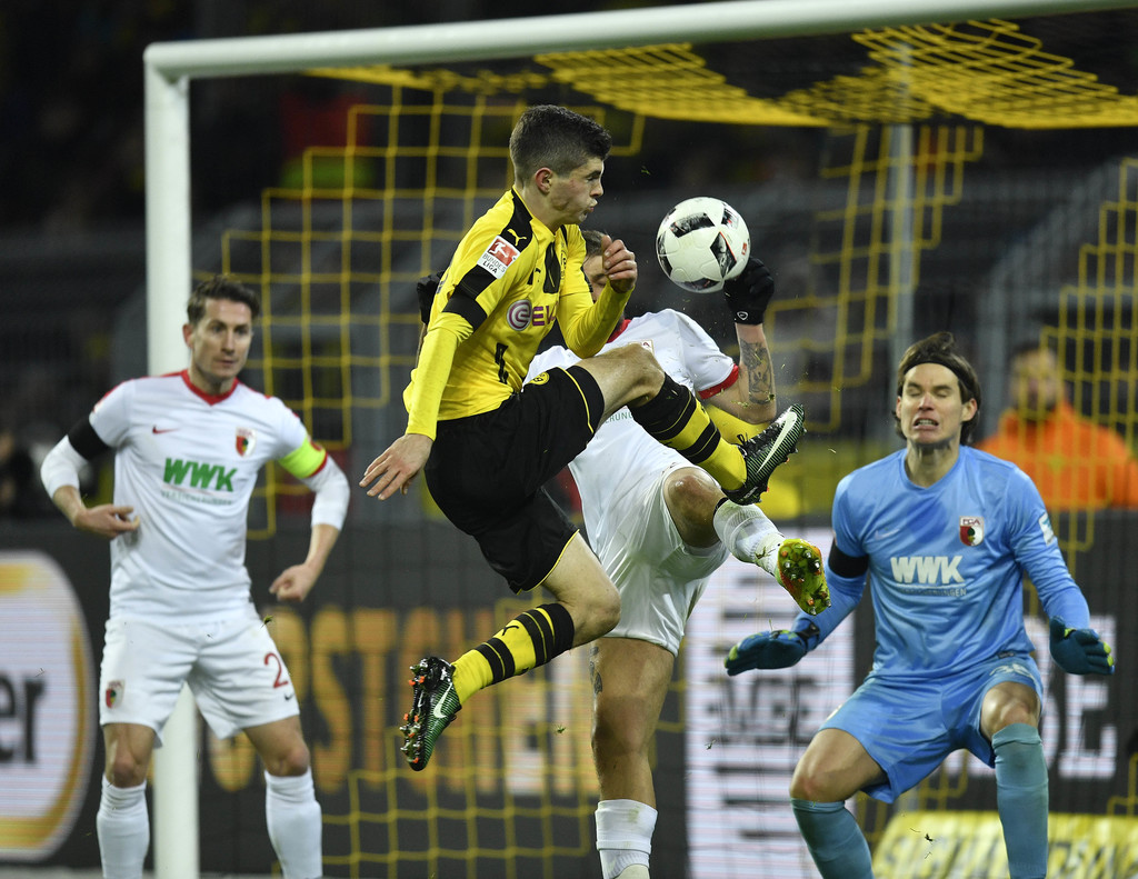 Dortmund's Christian Pulisic jumps for the ball in front of Augsburg goalkeeper Marwin Hitz during the German Bundesliga soccer match b...
