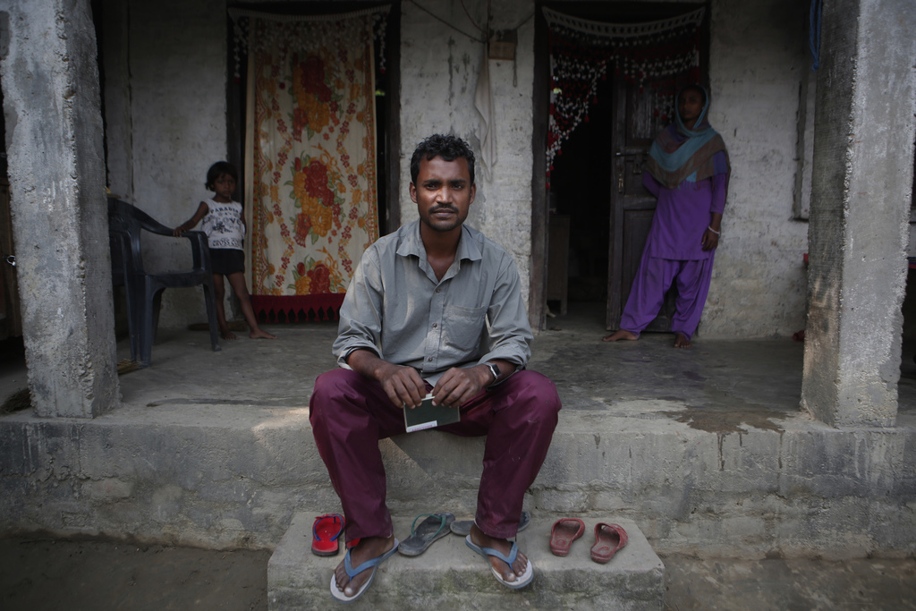 In this Nov. 23, 2016 photo, Mohammed Tohit, 28, holds his passport in front of the solid, cement and plaster home that he built for hi...