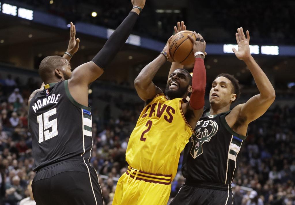 Cleveland Cavaliers' Kyrie Irving shoots between Milwaukee Bucks' Greg Monroe and Malcolm Brogdon during the first half of an NBA baske...