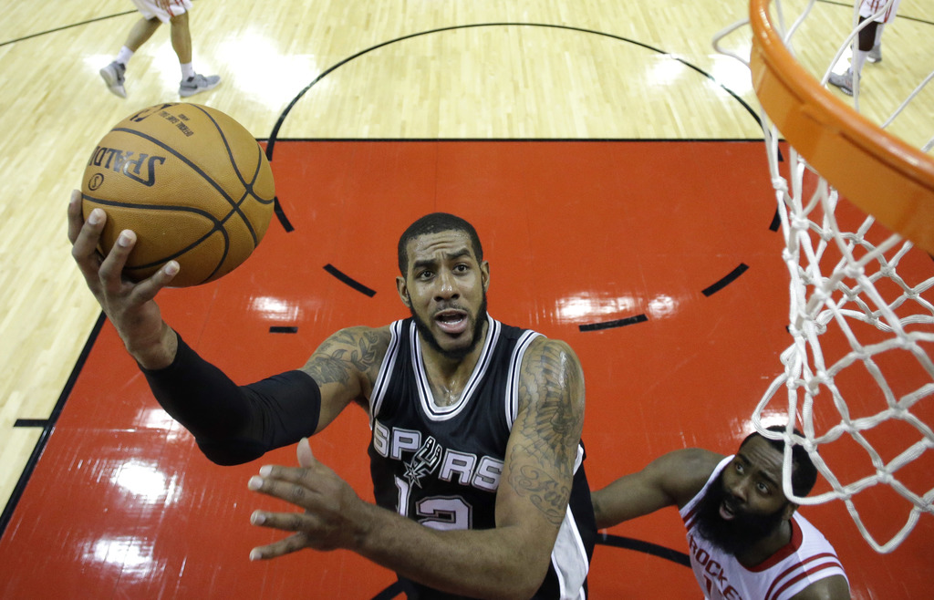 San Antonio Spurs' LaMarcus Aldridge (12) goes up for a shot as Houston Rockets' James Harden defends during the first half of an NBA b...