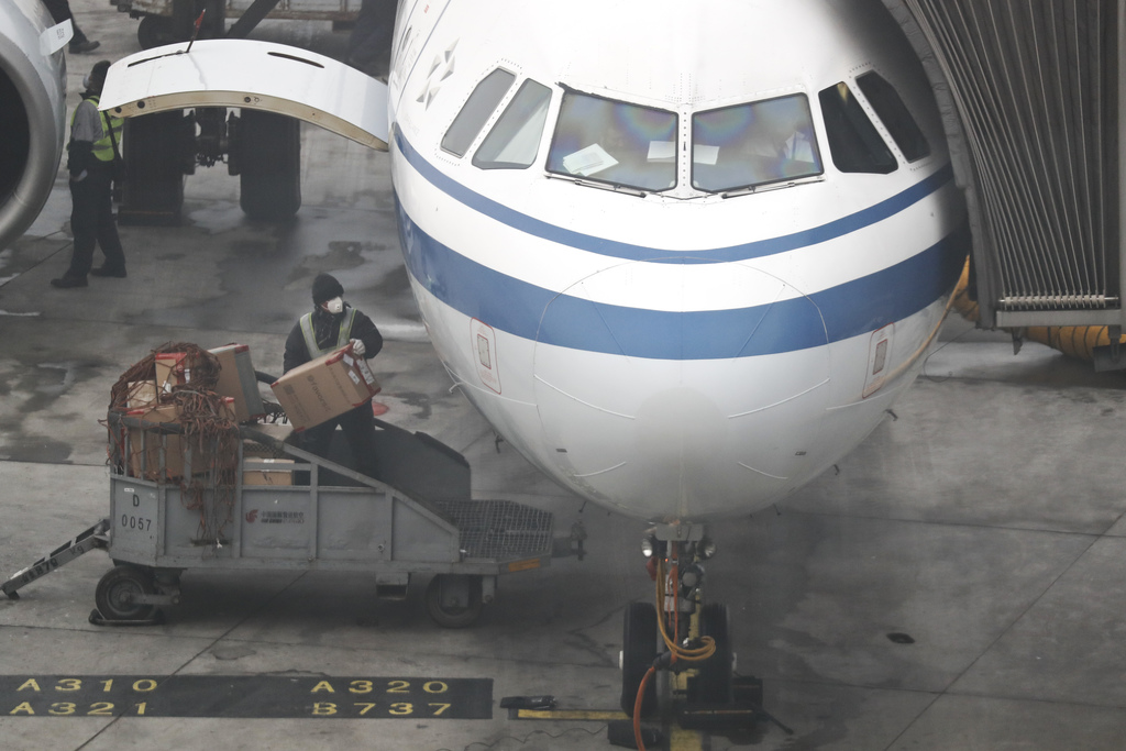 An airport worker wearing a mask for protection against air pollution loads goods on to an Air China passenger plane at the Beijing Cap...