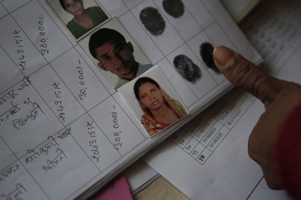 In this Tuesday, Dec 20, 2016 photo, Saro Kumari Mandal, 26, gives her fingerprint to receive compensation from the Foreign Employment ...