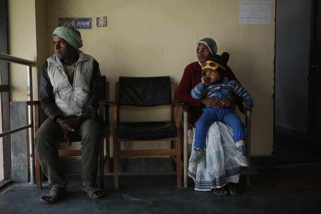 In this photo taken on Monday, Dec 19, 2016, Saro Kumari Mandal, 26, sits with her son and her father-in-law at the Department of Forei...