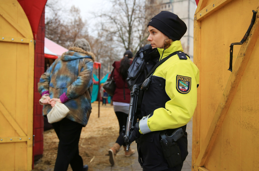 A police officer guards the entrance to a Christmas market in Magdeburg, Germany, Tuesday Dec. 20, 2016, one day after a truck ran into...