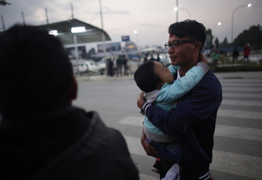 In this Monday, Nov. 28, 2016 photo, a Nepali migrant worker Krishna Bahadur Tamang, 32, carries his son before departing for Qatar at ...