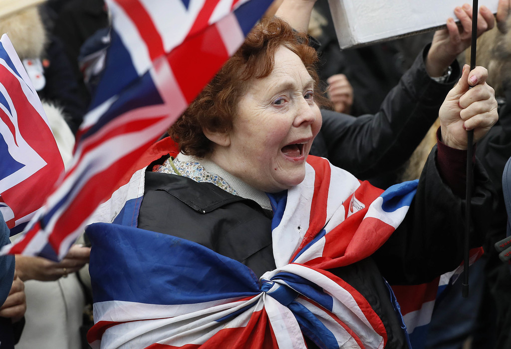 """FILE - In this Wednesday, Nov. 23, 2016 file photo, """"Brexit"""" supporters wave flags outside Parliament in London, timed to coincide with..."""