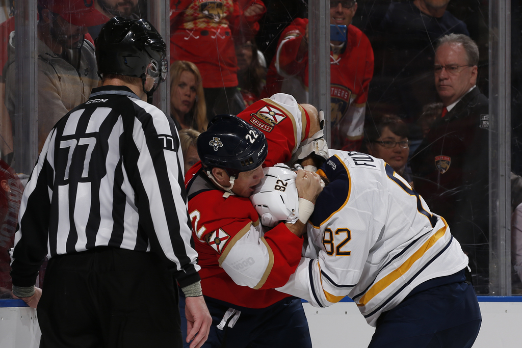 Linesman Tim Nowak (77) looks on as Florida Panthers right wing Shawn Thornton (22) and Buffalo Sabres left wing Marcus Foligno (82) fi...