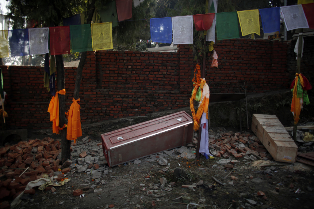 In this Monday, Nov. 29, 2016 photo, a red coffin that brought home the body of Nepali migrant worker from Saudi Arabia, lies on the gr...