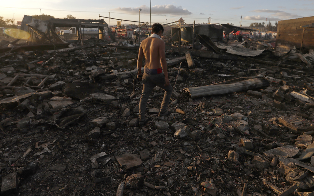 A man walks  through the scorched ground of the open-air San Pablito fireworks market, in Tultepec, outskirts of Mexico City, Mexico, T...