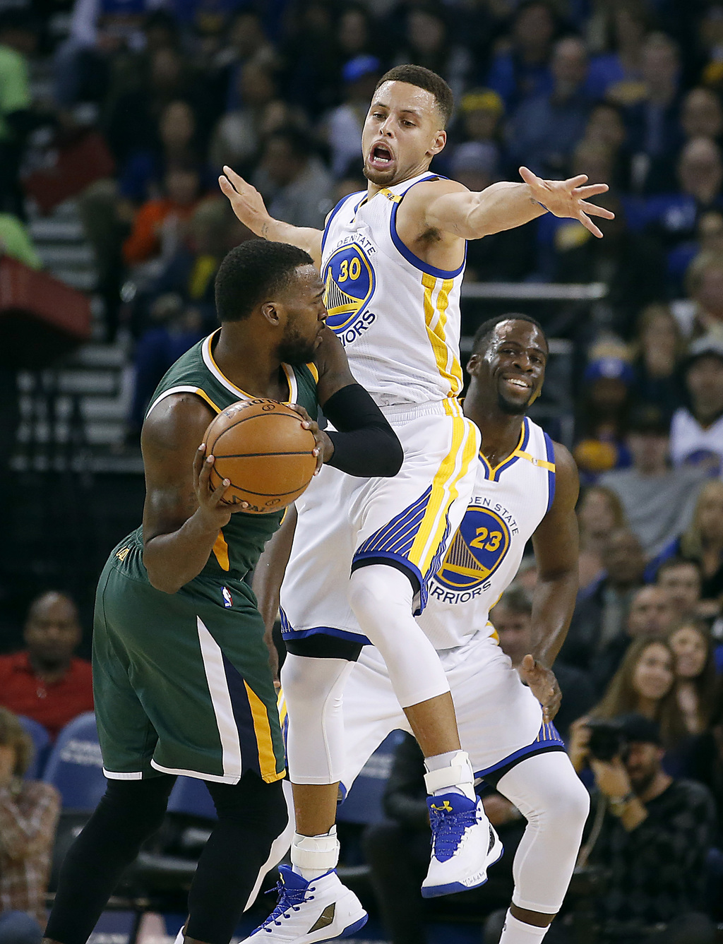 Golden State Warriors guard Stephen Curry (30) guards against Utah Jazz guard Shelvin Mack, left, during the first half of an NBA baske...