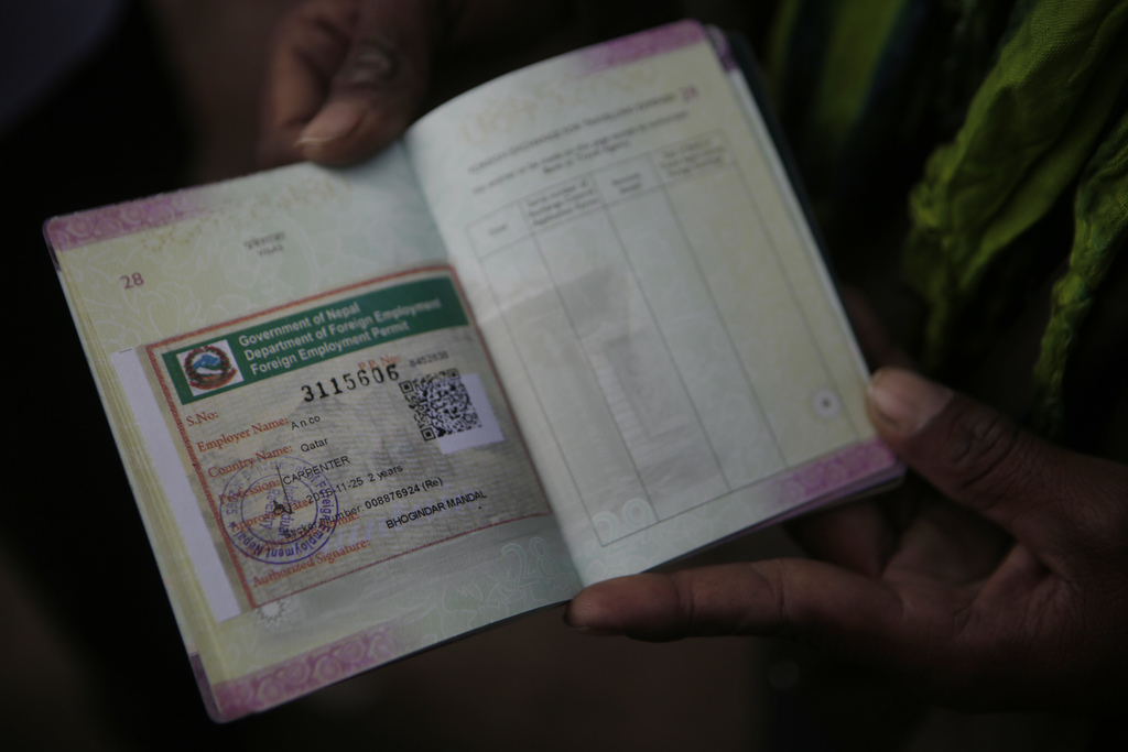 In this Nov 25, 2016 photo, a Nepalese man shows his passport with a working permit at the Department of Foreign Employment (DoFE) in K...