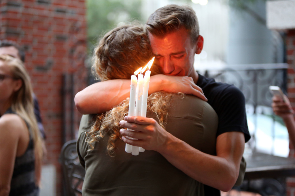 FILE - In this Sunday, June 12, 2016 file photo, Brett Morian hugs an fellow mourner during a candlelight vigil for those killed at the...
