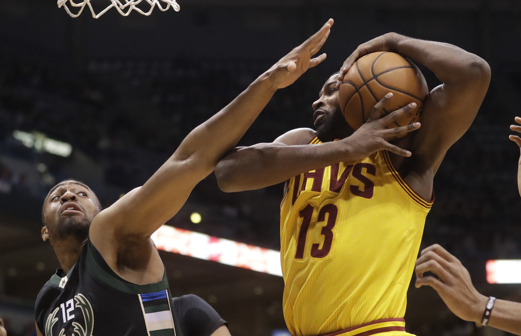 Cleveland Cavaliers' Tristan Thompson rebounds in front of Milwaukee Bucks' Jabari Parker during the first half of an NBA basketball ga...
