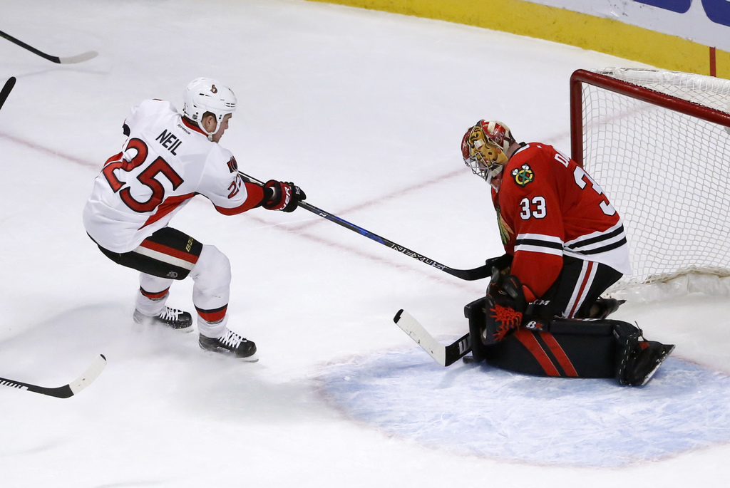 Chicago Blackhawks' Scott Darling (33) makes a save and keeps Ottawa Senators' Chris Neil from getting a rebound shot during the first ...