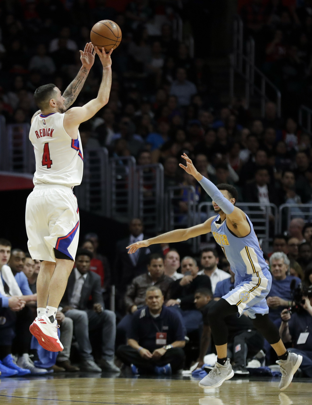 Los Angeles Clippers guard J.J. Redick, left, shoots over Denver Nuggets guard Jamal Murray during the second half of an NBA basketball...