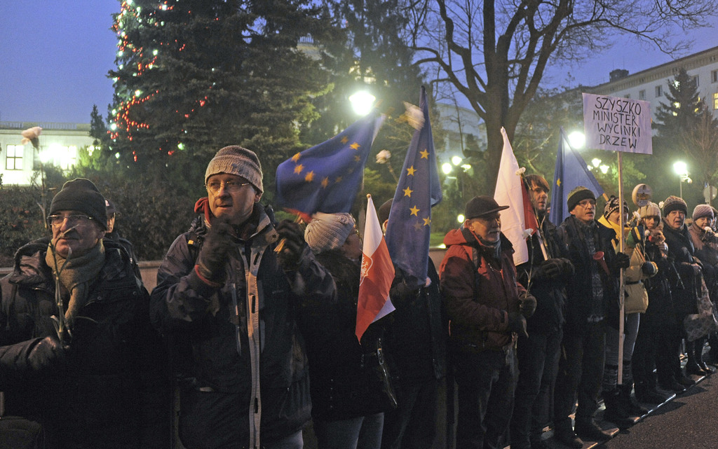 Protesters stand along a fence in front of the parliament. in Warsaw, Poland, Tuesday, Dec. 20, 2016. Although the ruling Law and Justi...