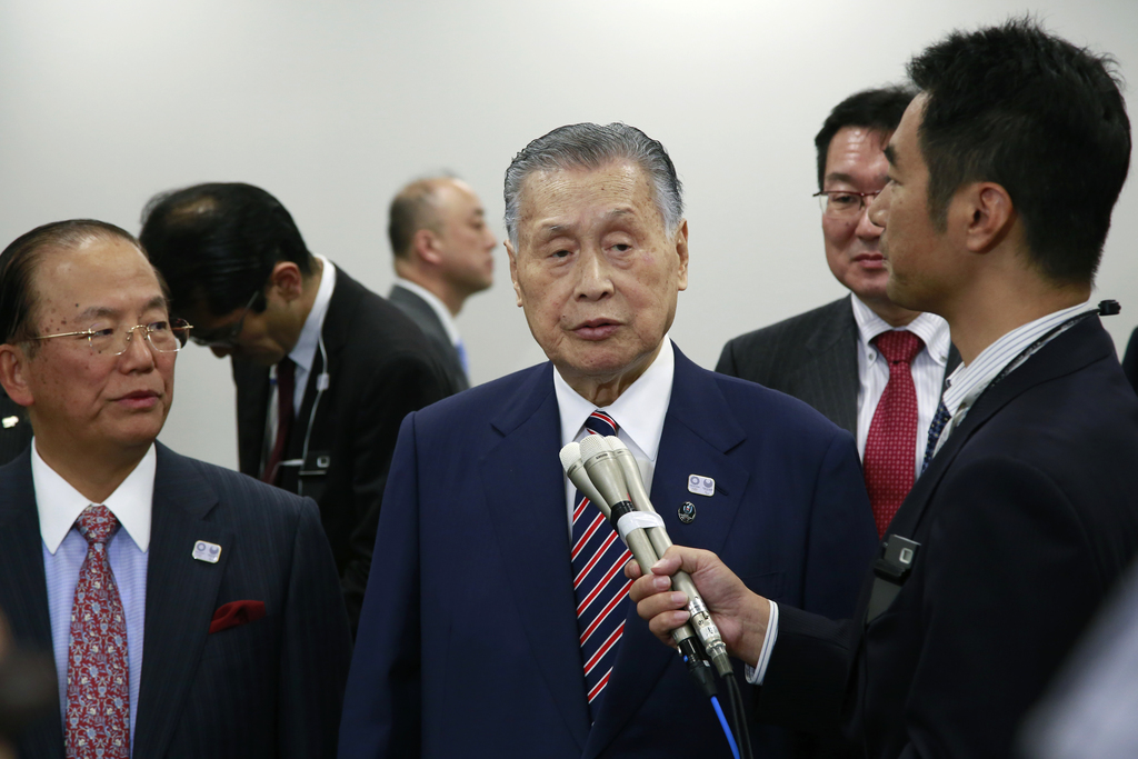 Tokyo Olympics Organizing Committee President Yoshiro Mori, center, answers a reporter's question after the four-party working group me...
