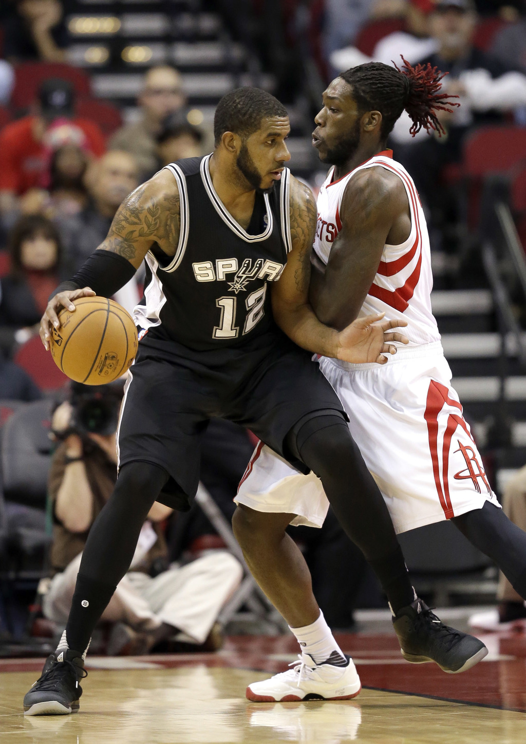 San Antonio Spurs' LaMarcus Aldridge (12) is guarded by Houston Rockets' Montrezl Harrell during the first half of an NBA basketball ga...