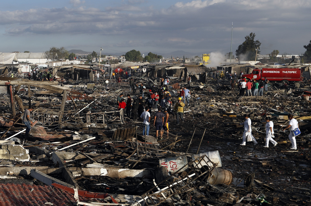 Firefighters and rescue workers walk through the scorched ground of Mexico's best-known fireworks market after an explosion explosion r...