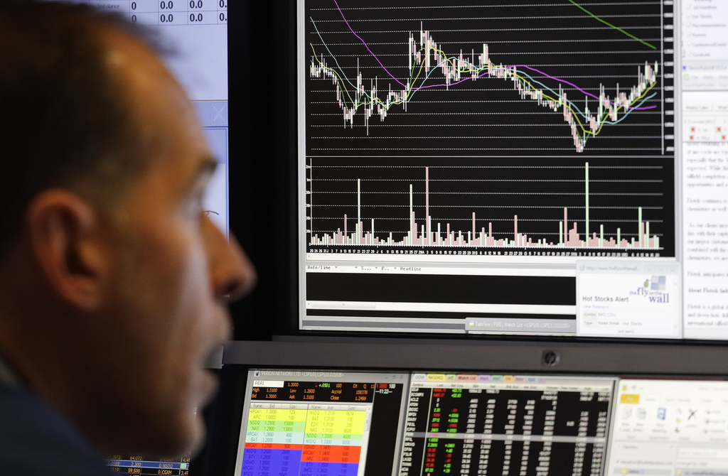 Stock trader Mark Puetzer follows stock information on electronic screens at the New York Stock Exchange, Tuesday, Dec. 20, 2016, in Ne...