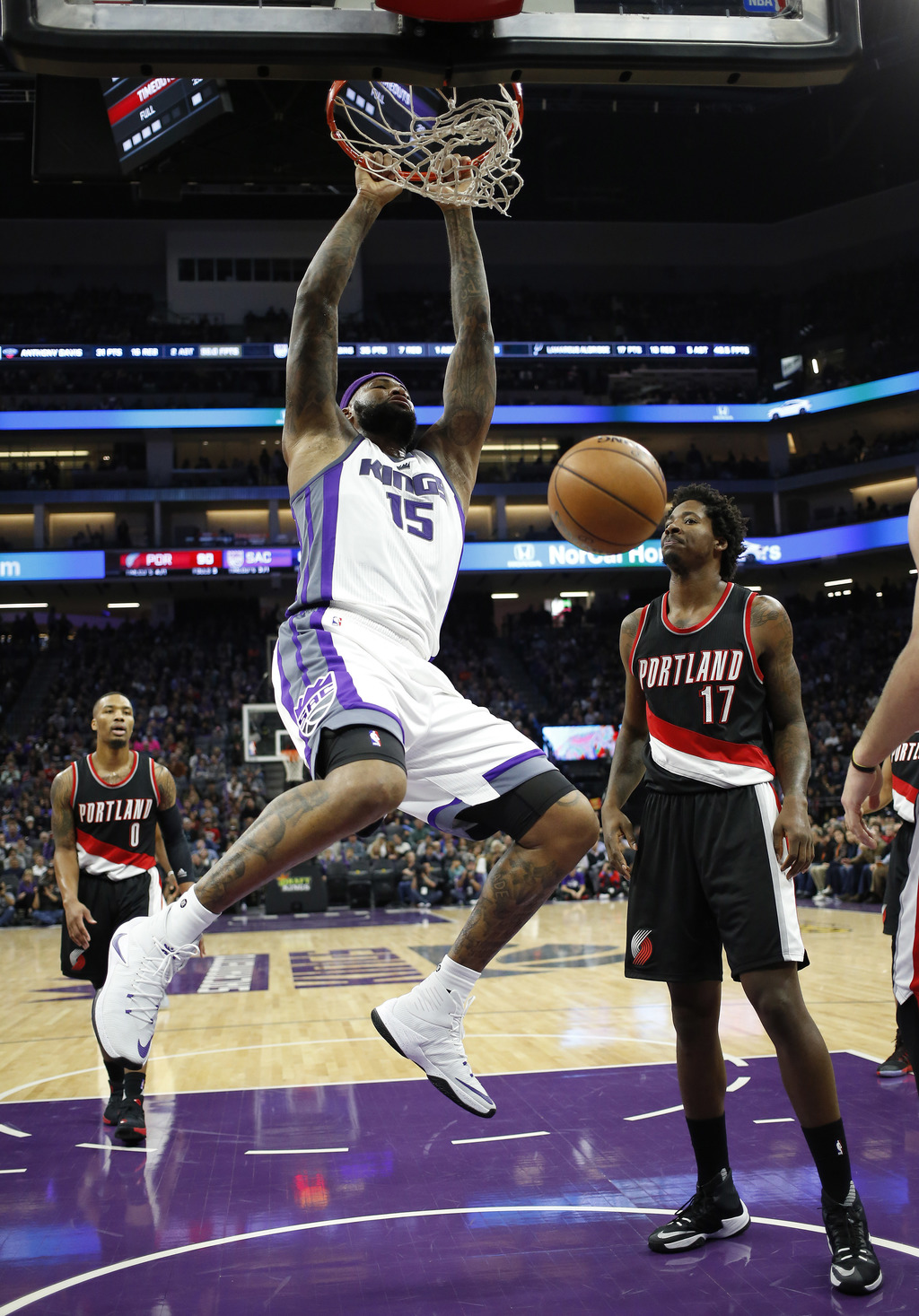 Sacramento Kings forward DeMarcus Cousins, center, hangs from the rim after dunking as Portland Trail Blazers' Damian Lillard, left, an...