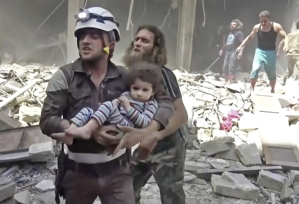 FILE - In this image made from video and posted online by Validated UGC on Thursday, April 28, 2016, a civil defense worker carries a c...