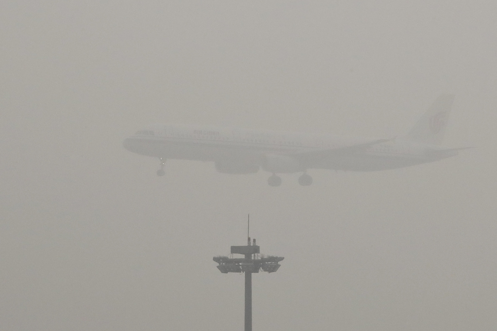 An Air China passenger plane prepares to land at the Beijing Capital International Airport as the capital of China through heavy smog o...
